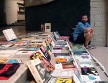 Artista vendiendo sus libros usados